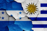flags of Honduras and Uruguay painted on cracked wall