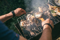 Hands of a man with a fork and a wooden spatula in the foreground. He is cooking delicious and fresh grilled fish with lemon on the Barbeque grill at the garden in summer. Selective focus macro shot with shallow DOF