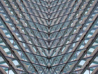 a full frame modern architectural abstract with futuristic geometric angular reflected shapes and lines in blue glass and steel