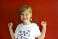Pretty emothional child on a red background. Copy space, daylight