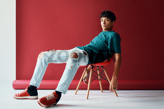 Stylish handsome young man relax and posing on studio sitting on a chair looking to camera.