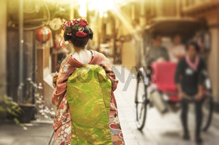 Maiko walking in an alley of Kyoto in the sunset light crossing a rickshaw.