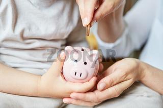 Mutter und Kind stecken Geldstück in Sparschwein
