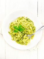 Pasta with pesto sauce in plate on light board top