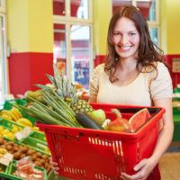 Frau trägt Einkaufskorb im Supermarkt