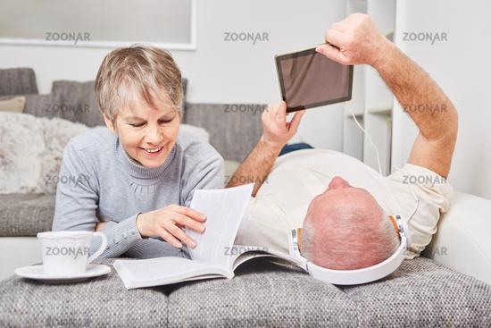 Paar Senioren lesen Buch als Ebook und auf Papier