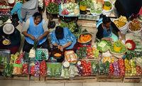CUENCA, ECUADOR - 2-12-2015: Women work at a market selling fresh vegetables in Cuenca Ecuador