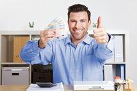 Manager mit Geld hält Daumen hoch