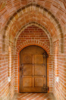 Wooden door in a brick tunnel, close up
