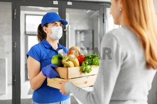 delivery girl in mask giving box of food to woman