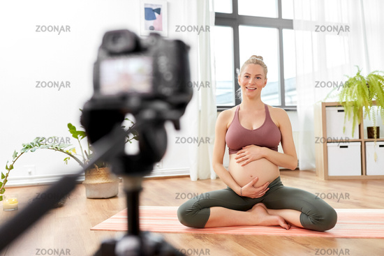 pregnant woman or yoga blogger with camera at home