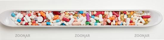 Bunte Medikamente in einer länglichen Schale