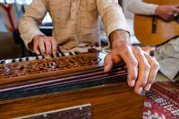 Male playing keys on harmonium