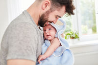Vater trocknet Baby nach Baden mit Handtuch
