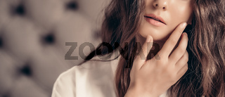 Beautiful woman applying cosmetics with her hand on face, natural look and wavy long hairstyle, beauty portrait and skincare routine