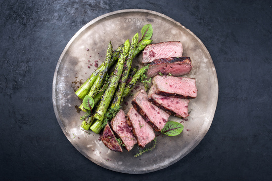 Barbecue dry aged wagyu roast beef steak with green asparagus and lettuce offered as top view on a rustic modern design plate