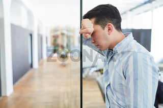 Junger Business Mann im Büro mit Burnout