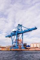Massive blue crane unload cargo in a seaport in Sweden