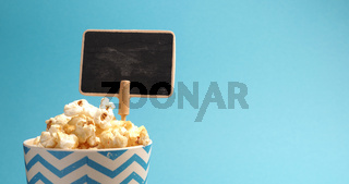 Fresh popcorn on a blue background with space for text