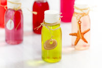 Small bottles of colorful cosmetic oils with marine decorations