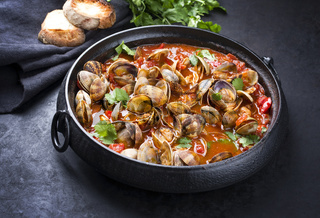 Cooked Japanese carpet shell with paprika and baguette in spicy tomato garlic sauce as closeup in a modern design pot