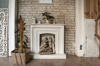 White fireplace in a brick wall. There's wood in the fireplace. Nearby wicker basket with decorative dry plants. High quality photo