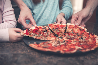 Family eating pizza at home