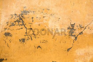 Grunge plastered wall with cracks. Yellow color retro stucco. Close up shot. Abstract texture or background