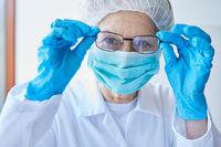 Frau als Arzt in Schutzkleidung mit Mundschutz