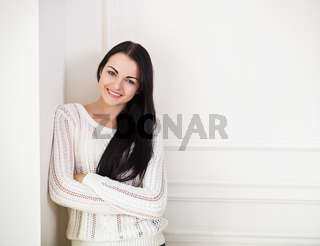 Happy brunette teen girl near the wall in the room