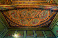 Ceiling at royal era historic Manasterly Palace decorated with colorful and golden floral paintings