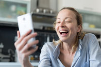 Young smiling cheerful pleased woman indoors at home kitchen using social media apps on mobile phone for chatting and stying connected with her loved ones. Stay at home, social distancing lifestyle.
