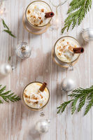 Traditional eggnog with cinnamon and nutmeg for Christmas and winter holidays. With Xmas decorations on wooden background.