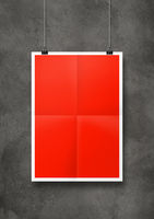 Red folded poster hanging on a concrete wall with clips