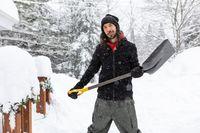 a man standing outdoor holding a shovel.
