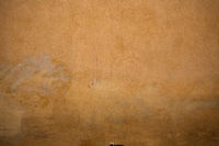 Painted stucco texture. Yellow or orange plastered wall of an old building. Exterior of retro architecture