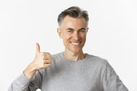 Close-up of handsome, confident middle-aged man in gray sweater, showing thumbs-up in approval, recommending something, standing over white background
