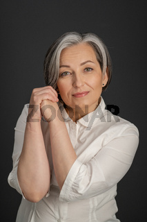 Aged woman charmingly smiles tilting head slightly and clasped hands near face. Beautiful lady in white shirt Isolated on gray