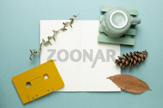 Open empty notebook with mug cup, audio cassette tape, dry plant on green background. autumn and winter concept. top view, copy space
