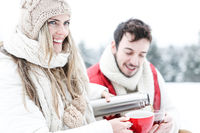 Paar trinkt Tee unterwegs im Schnee