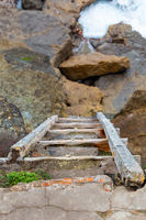 old wooden ladder on rock cliff on ocean coast