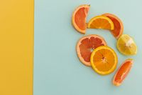 Slices of grapefruit, orange and lemon on blue and yellow background