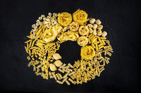 Italian pasta wreath with copy space, a flat lay of a variety of pasta types, shot from the top on a black background with a place for text