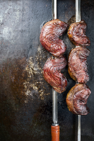 Barbecue dry aged wagyu Brazilian picanha from the sirloin cap of rump beef offered as closeup on a skewer on a rustic old board with copy space left