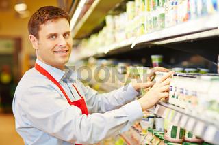 Verkäufer sortiert Molkereiprodukte im Supermarkt