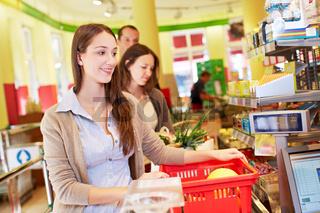 Frau bezahlt an Supermarktkasse