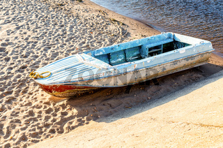 Old metal fishing boat on the bank of the river