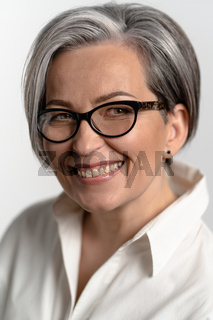 Pretty gray haired woman smiling at camera. Mature woman in eyeglasses and white shirt broadly smiles. Business concept. Education concept. Close up portrait