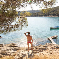 Rear view of man wearing red speedos tanning and realaxing on wild cove of Adriatic sea on a beach in shade of pine tree.