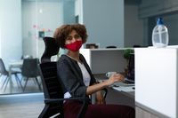 Mixed race woman wearing face mask in office